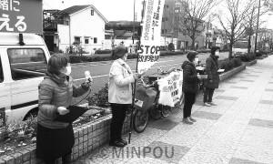 公園前でマイク宣伝する「西成区民アクション」のメンバー=3月29日、大阪市西成区内