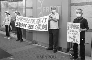 「何で今やる?コロナ対策に集中せよ」と書かれた横断幕を掲げながら宣伝する参加者=13日、寝屋川市内