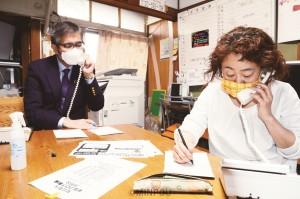 新型コロナ問題の電話相談に応じる長岡氏(右)と宮本氏(左)=4月27日、大阪市東淀川区内