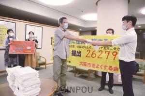 大阪市議会事務局に署名を提出する、よくする会の福井朗事務局長(中央)=12日、大阪市役所内