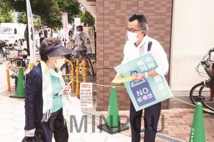 ビラを配りながら対話する市民=20日、大阪市西区内