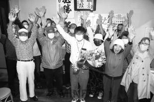 6期目の当選を果たし、支援者らと万歳をする力武氏(中央)=9月27日、河南町内